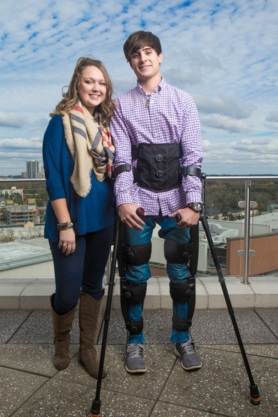 man wearing exoskeleton and using crutches stands next to able-bodied woman