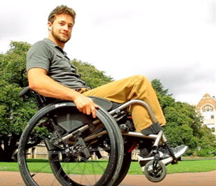 man in wheelchair with front wheels off the ground, demonstrating a wheelie