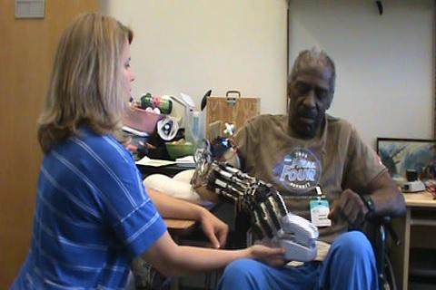 An occupational therapist assists a patient with therapy exercises using the X-glove. The patient is wearing the glove on his right hand and grasping a telephone handset.