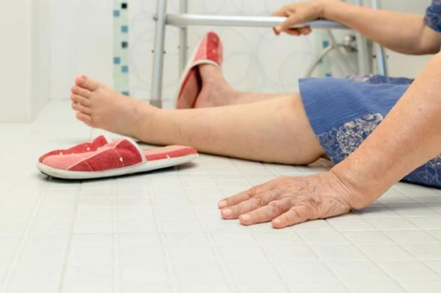 lady is sat on floor of bathroom holding zimmer frame after having a fall