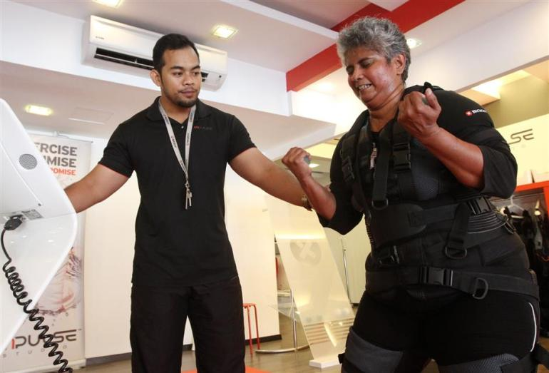 Trainer Mumahad Alif Ikhwan guiding a client on the bicep curls. -- SAMUEL ONG/The Star