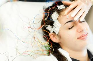 woman with electrodes attached to skull]
