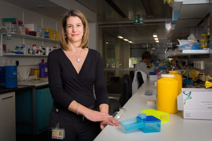 Dr Coralie English stands next to a laboratory bench.